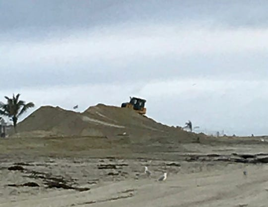 A bulldozer sits atop a sand pile as it builds a berm to protect a Sea Bright Beach club from winter storms. Reader submitted photo