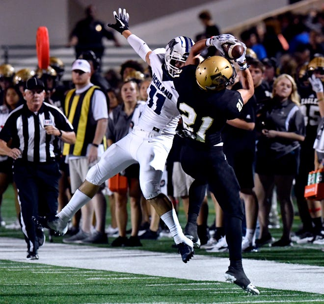 Abilene High's Reese Pettijohn makes a successful mid-air catch despite the coverage from Richland High's Brice Kirkland during Friday's game at Shotwell Stadium Sept. 28, 2018.  Final score was 48-41, Abilene.