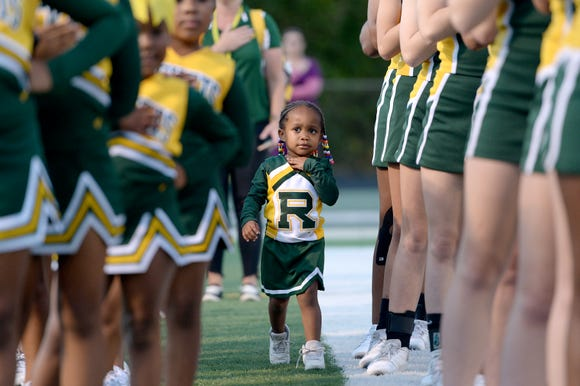 Tiny cheerleader Ar'Laya Smith, 2, makes her way through rows of older cheerleaders during the playing of the National Anthem before the start of Reynold's game against Tuscola at Reynolds High School on Sept. 28, 2018.