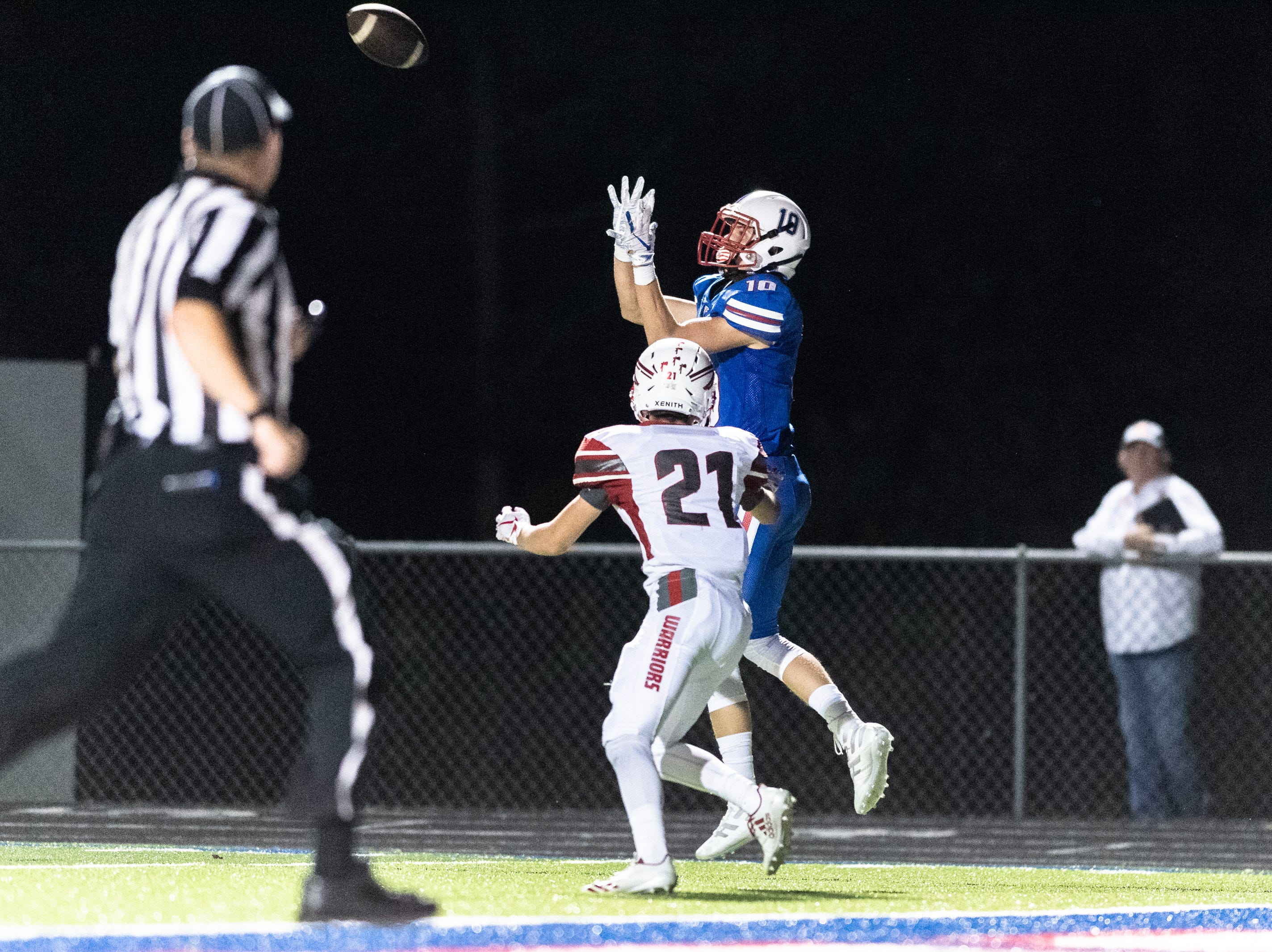 West Henderson's TJ Fink makes a catch, running the ball in for a touchdown past Erwin's Mason Eppler during their game Sept. 28, 2018.