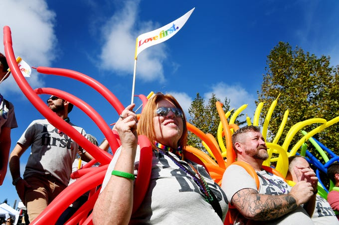 """Candace Ashby holds a flag reading """"love first"""" at the Blue Ridge Pride Festival in downtown Asheville Sept. 29, 2018."""