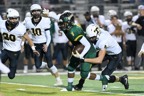 Reynolds' I'dre Bell gets taken down by Tuscola's Zane Edwards as he runs the ball during their game at Reynolds High School on Sept. 28, 2018. Bell was injured on the play and was carried off the field.