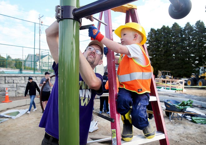 Henry Speare, 4, helps his dad Bryan install playground equipment at Manette Park in Bremerton.