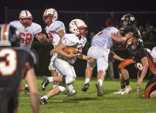 Rutland's Ryan Moore carries the ball against Middlebury during Friday night's high school football game in Middlebury.