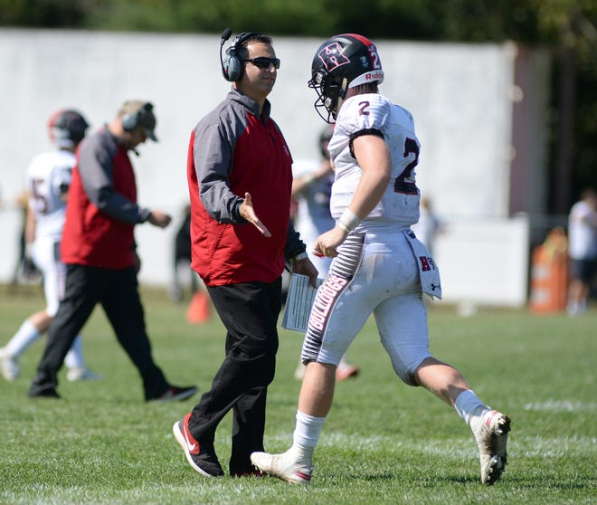Haddonfield quarterback Jay Foley high fives coach Frank DeLano after throwing a touchdown earlier this season in a win over St. Joseph. The Haddons host Camden High on Friday night for the South Jersey Group 2 title.