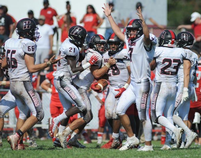 Haddonfield players celebrate after Lewis Evans intercepts a St. Joseph pass to seal a 22-15 victoryduring Saturday's game, Sept. 29, 2018.