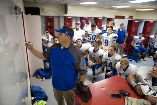 Southeastern head football coach Evan Gallaugher discusses the game plan in the locker room with his team in a win at Zane Trace in 2018.