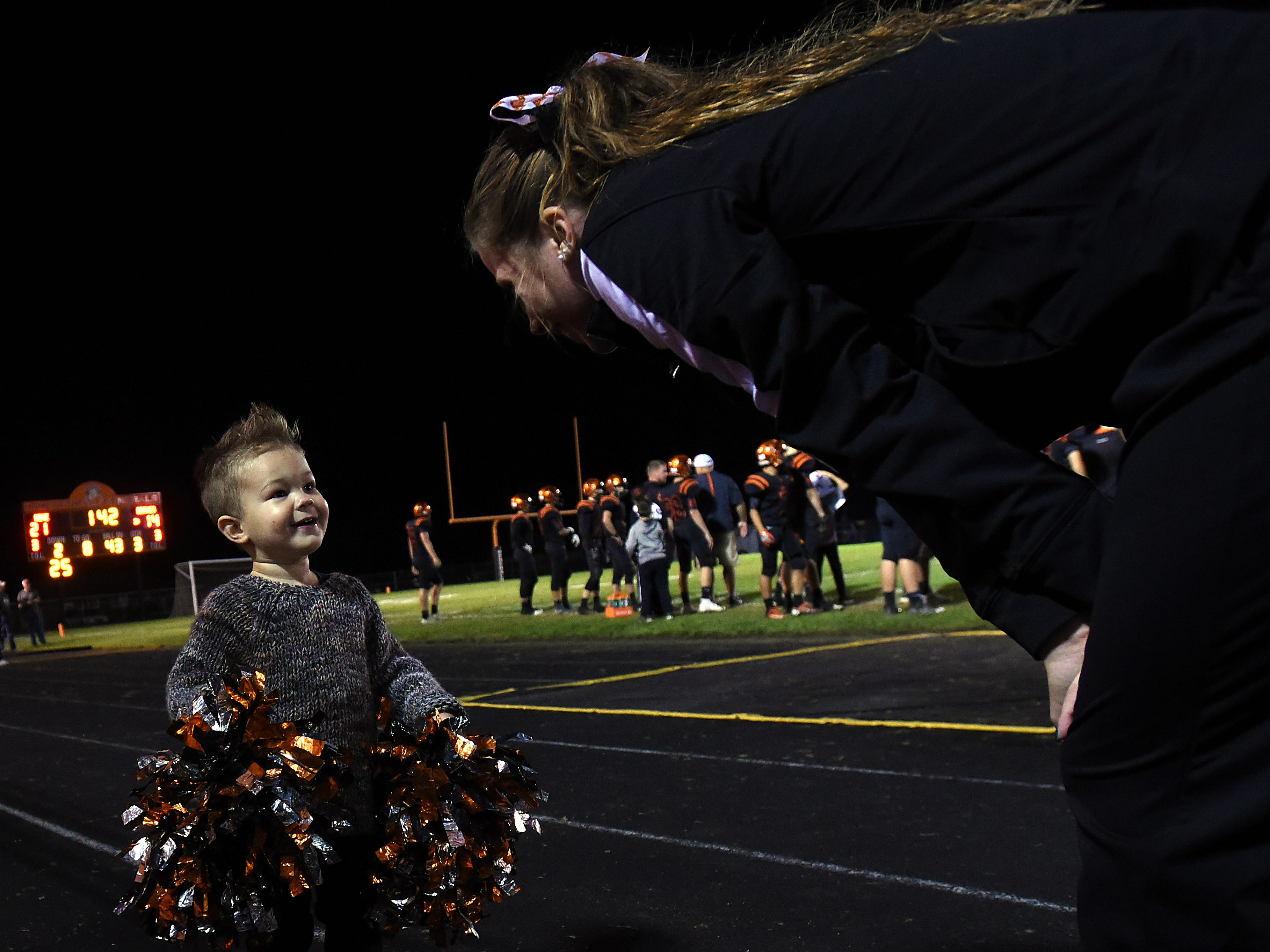 Ridgewood senior cheerleader Alexis Prater (right) tries to get Titan Stipes (left) to wave a set of pom noms during Friday night's football game.