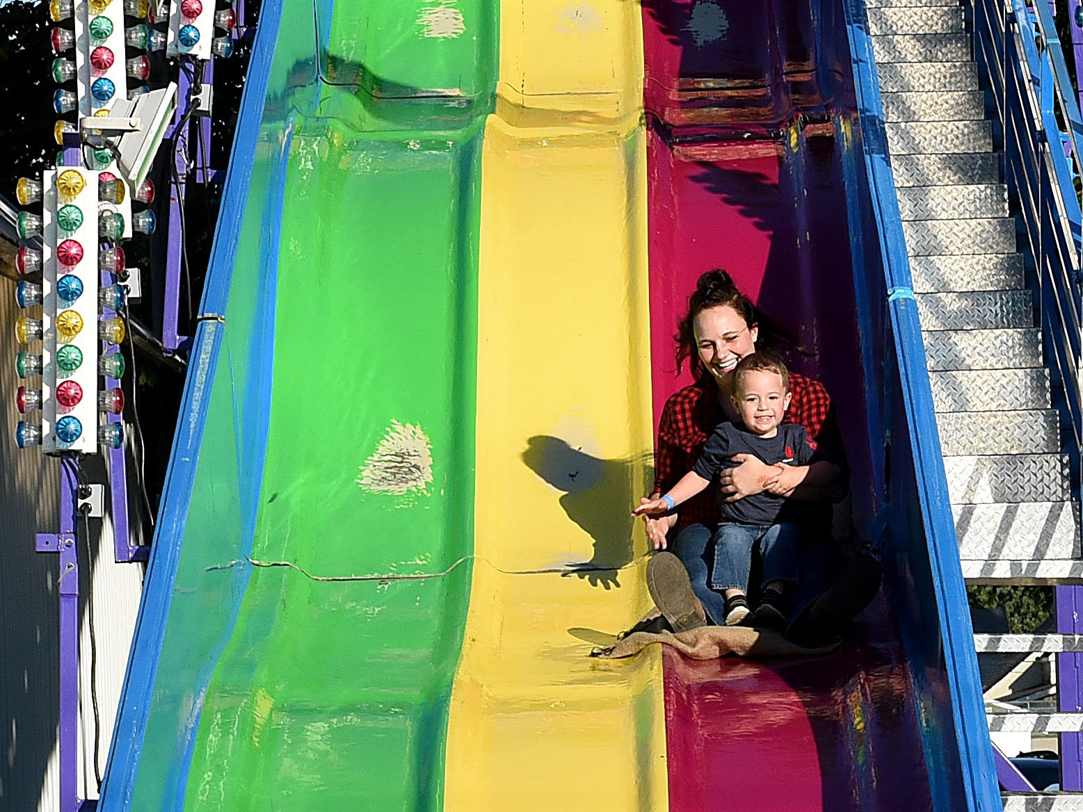 Kayla Mizer goes down the giant slide with son Cooper Mason at the Coshocton County Fair on Friday, Sept. 28, 2018.