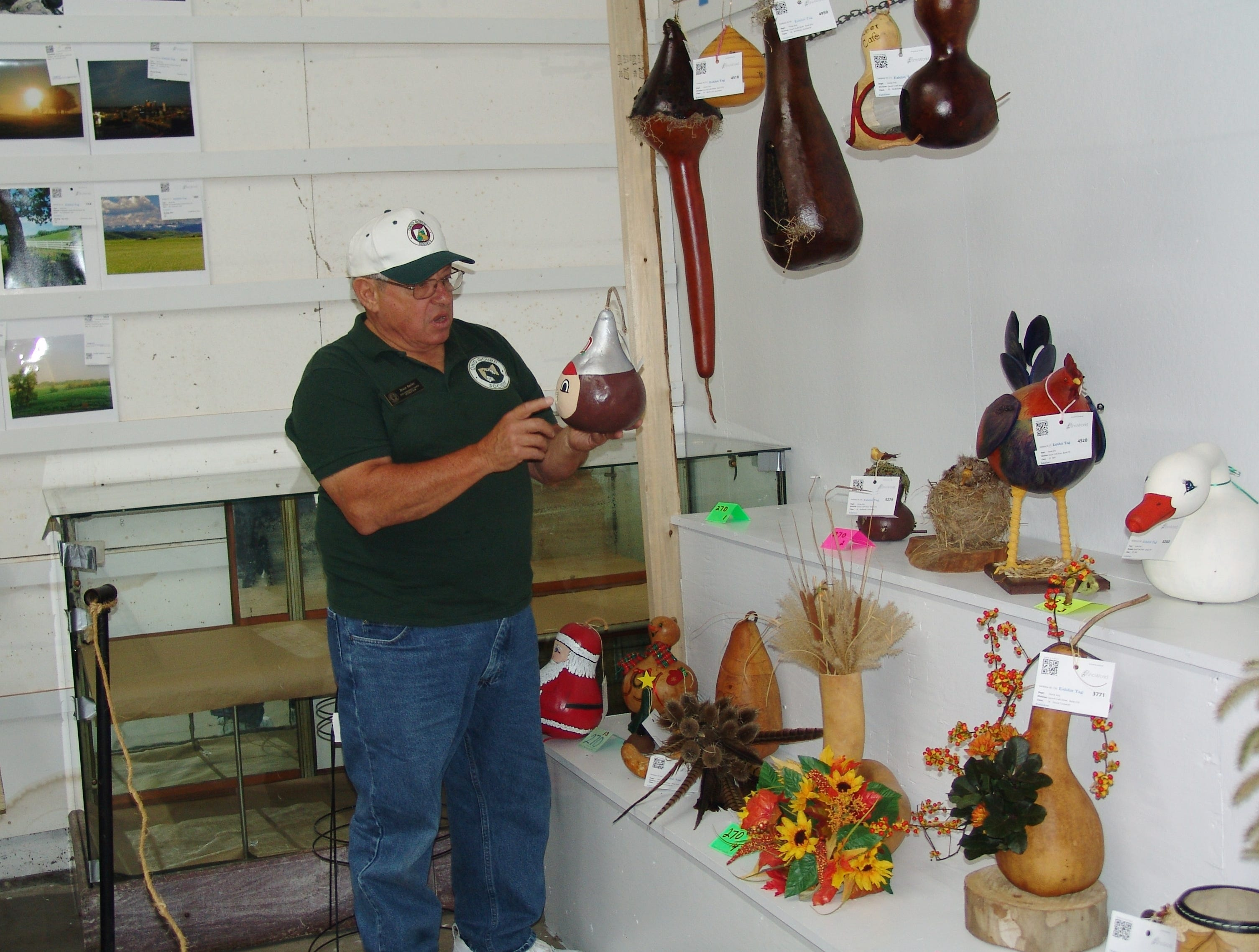 Gourd judge Bruce Barber looks at decorative gourd birdhouse during Friday's judging.