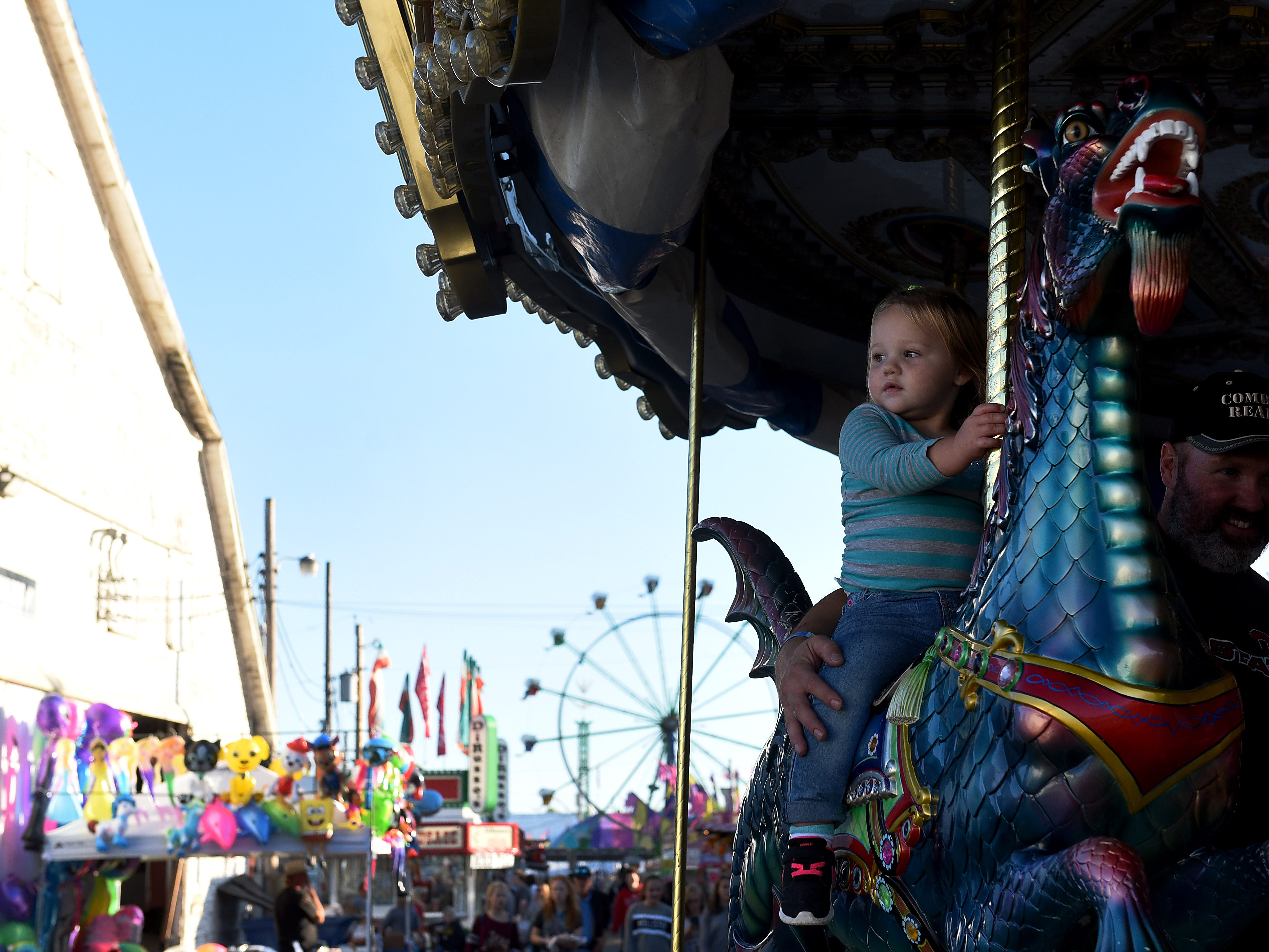 Sophia Lewis rides the carousel with her father, Chris Lewis, at the Coshocton County Fair on Friday, Sept. 28, 2018.