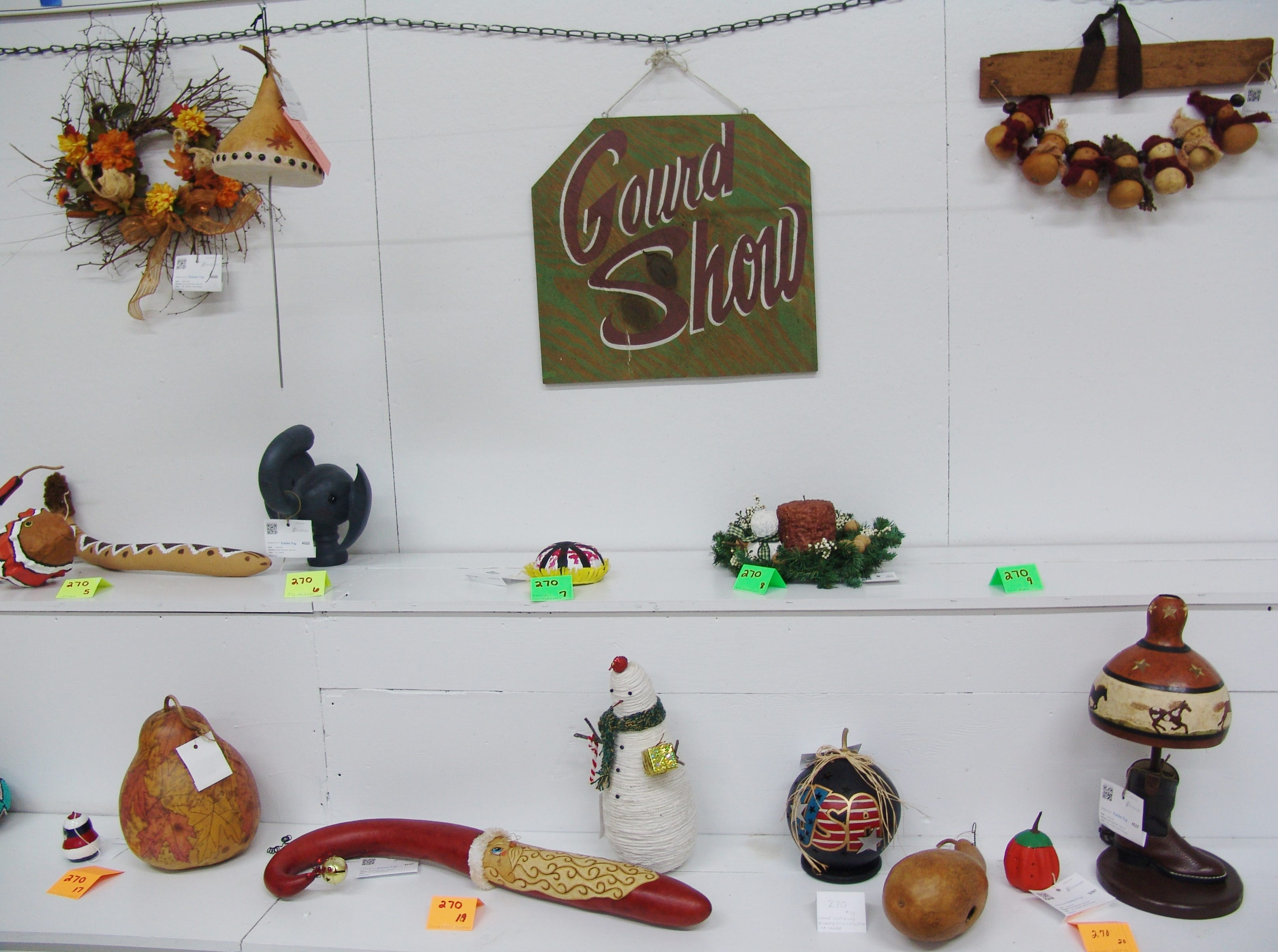 Exhibits in the Gourd Craft Show line a table in the Art Hall before Friday's judging.