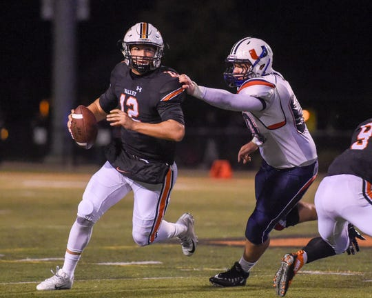 Valley Quarterback Beau Lombardi (12) scrambles under the pressure of Urbandale Defensive Lineman Sam Petrillo on Friday, Sept. 28, 2018 during a football game between the Valley Tigers and the Urbandale J-Hawks at Valley Stadium.