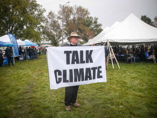 A voter concerned about climate issues holds a sign asking for candidates to discuss climate issues during the 2018 Polk County Steak Fry on Saturday, Sept. 29, 2018.