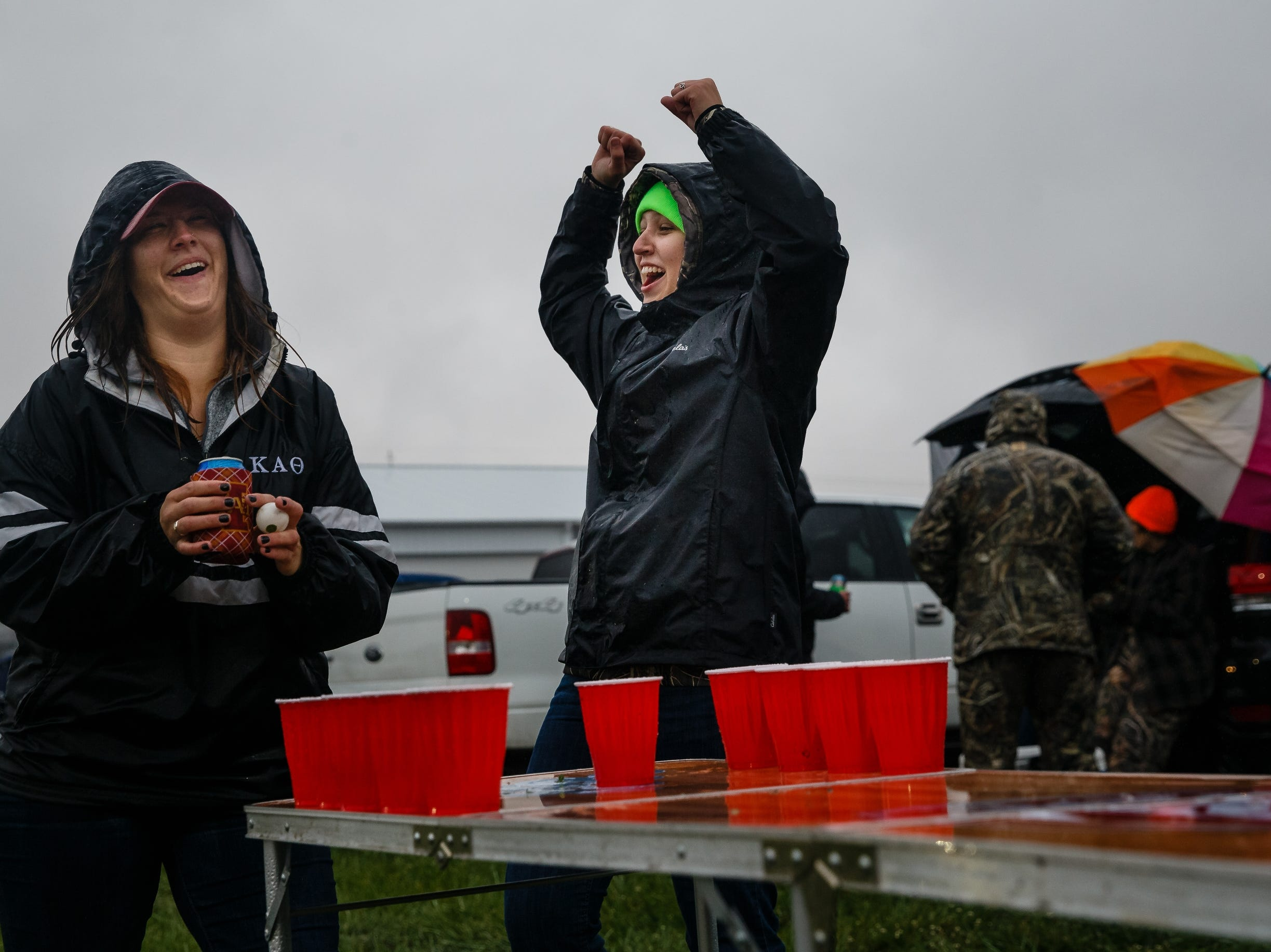 Allison Lane, 19 of Des Moines, celebrates a winning throw as she and her sister Megan Lane, 28 of Des Moines, left, try to stay dry and have fun before the start of Luke Bryan's Farm Tour on Saturday, Sept. 29, 2018 in Boone.