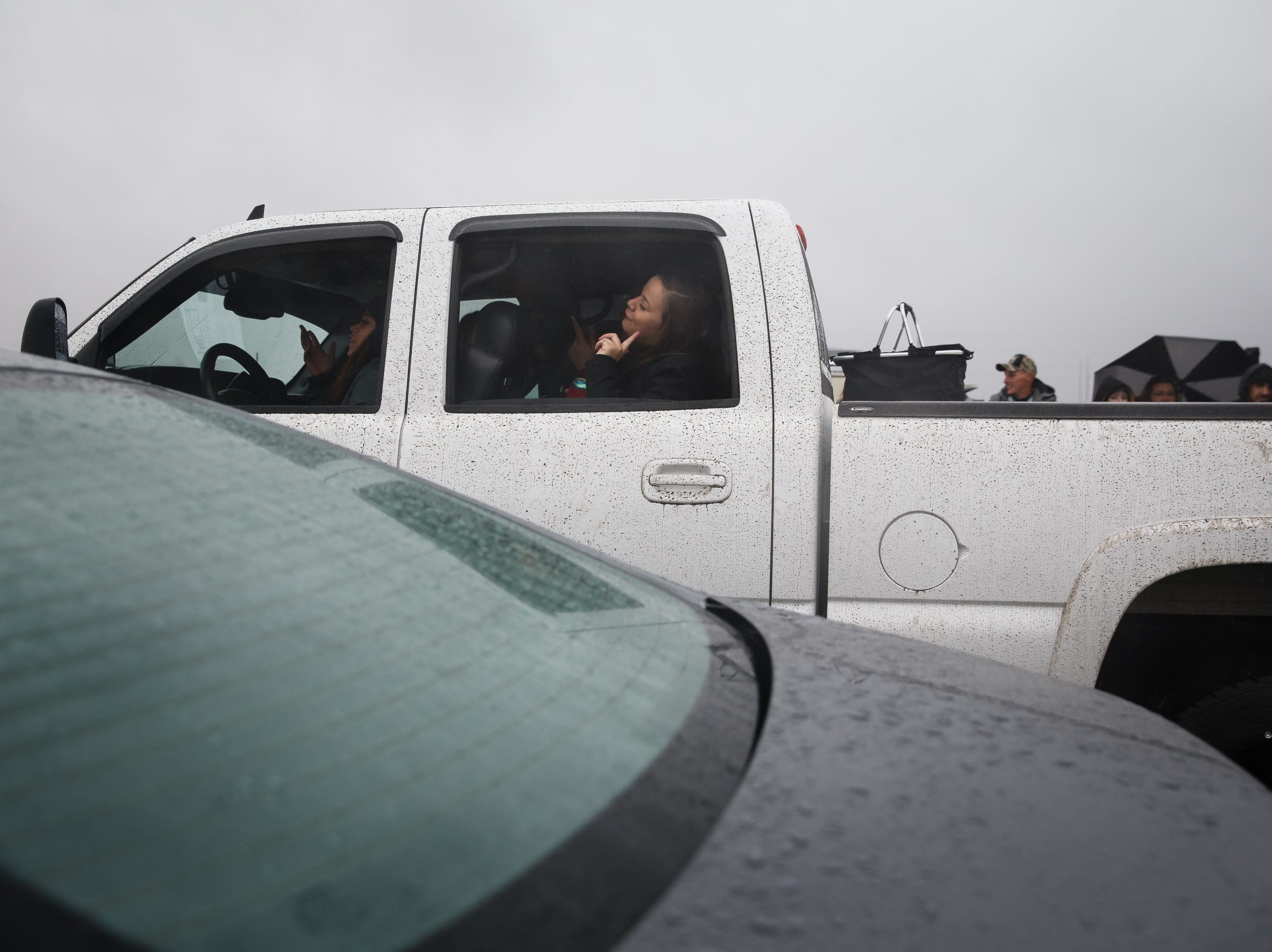 Megan Nemec, 19 of Fairfax, IA, sings while avoiding the rain in a friends truck before the start of Luke Bryan's Farm Tour on Saturday, Sept. 29, 2018 in Boone.