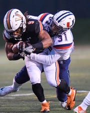 Valley's Creighton Mitchell (9) runs the ball as Urbandale's Jaden Harrell (31) defends on Friday, Sept. 28, 2018 during a football game between the Valley Tigers and the Urbandale J-Hawks at Valley Stadium.