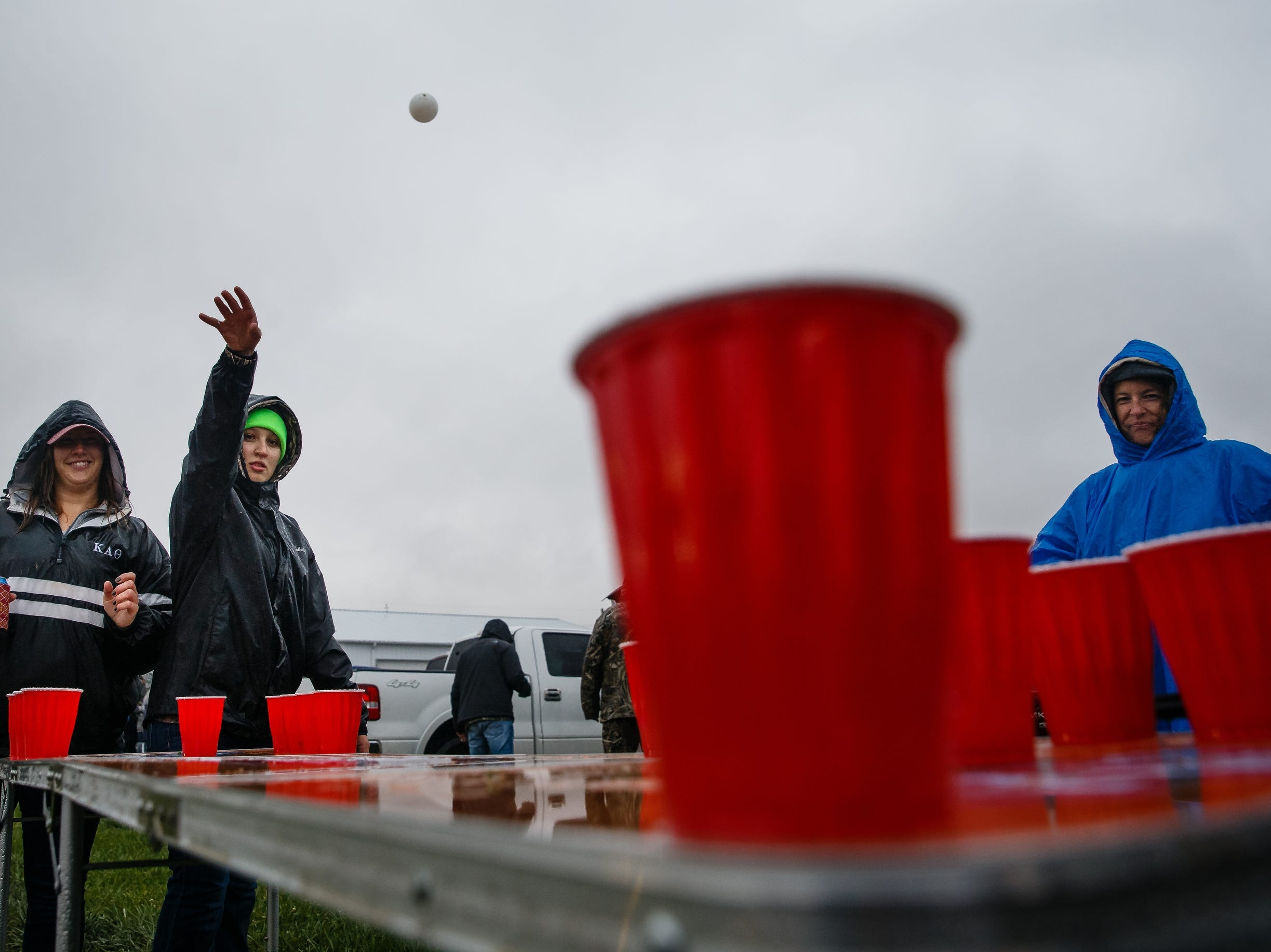 Allison Lane, 19 of Des Moines, throws a ping-pong ball as she and her sister Megan Lane, 28 of Des Moines, left, try to stay dry and have fun before the start of Luke Bryan's Farm Tour on Saturday, Sept. 29, 2018 in Boone.