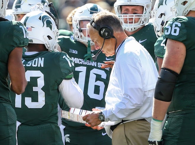 Michigan State coach Mark Dantonio talks to his players during a time out during the first half on Saturday, Sept. 29, 2018, at Spartan Stadium.