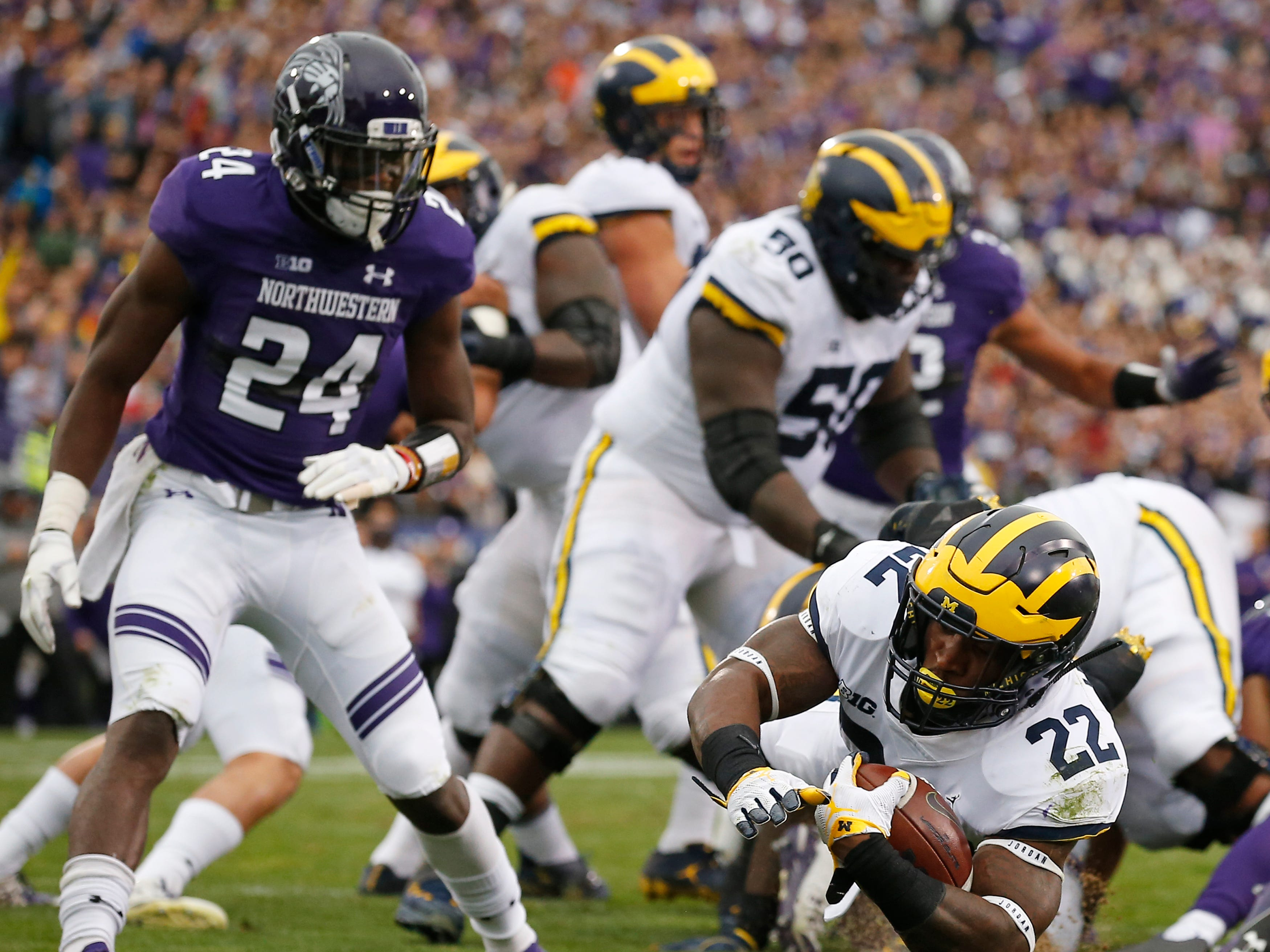 Michigan's Karan Higdon dives for a touchdown against Northwestern's Montre Hartage during the first half Saturday, Sept. 29, 2018, in Evanston, Ill.