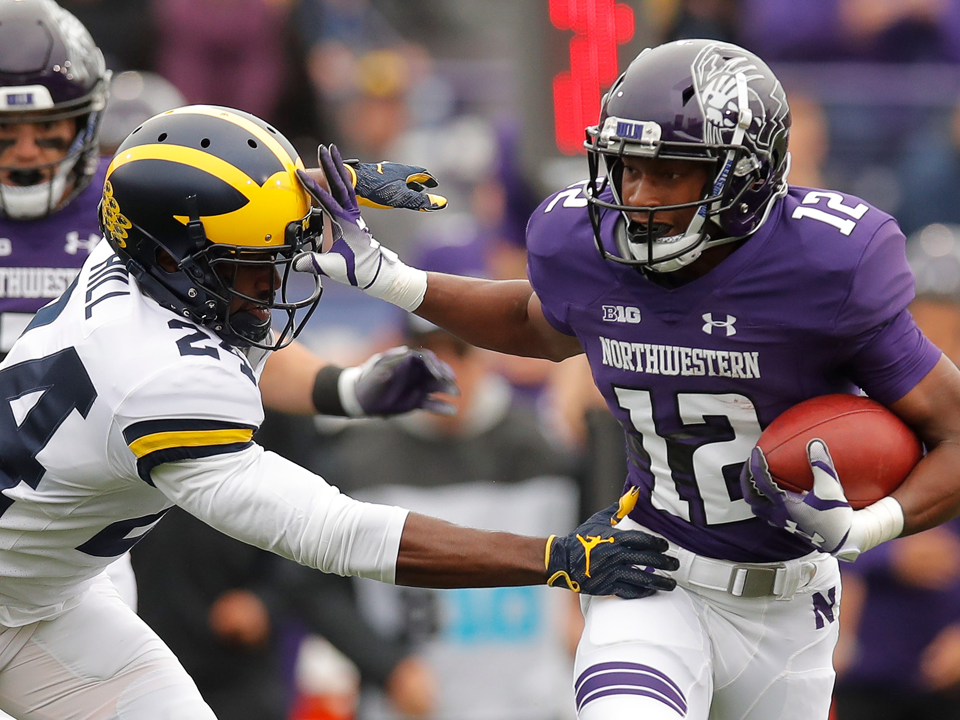 Northwestern's JJ Jefferson pushes off a tackle by Michigan's Lavert Hill during the first half Saturday, Sept. 29, 2018, in Evanston, Ill.