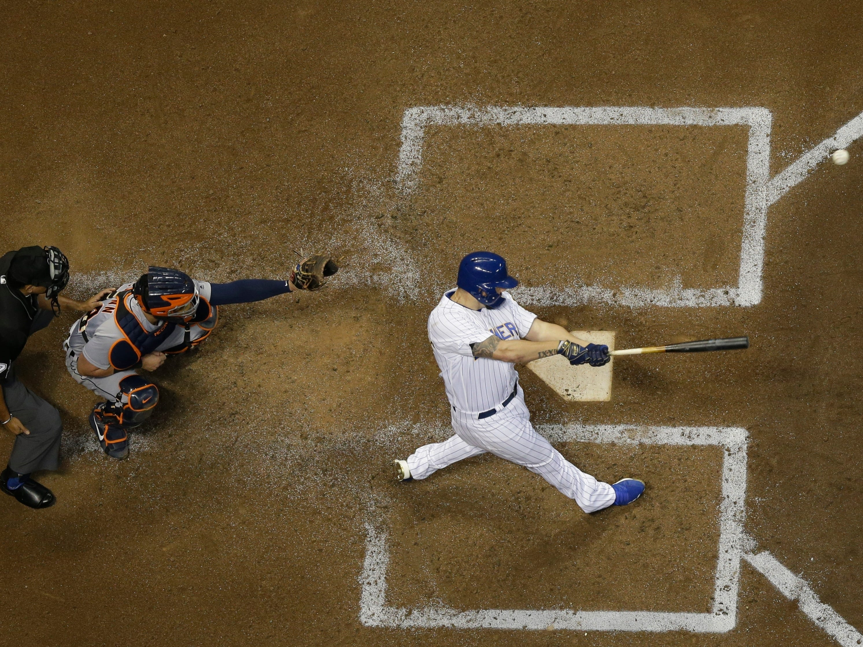 Milwaukee Brewers' Mike Moustakas hits an RBI single during the third inning against the Detroit Tigers, Friday, Sept. 28, 2018, in Milwaukee. James McCann is catching.