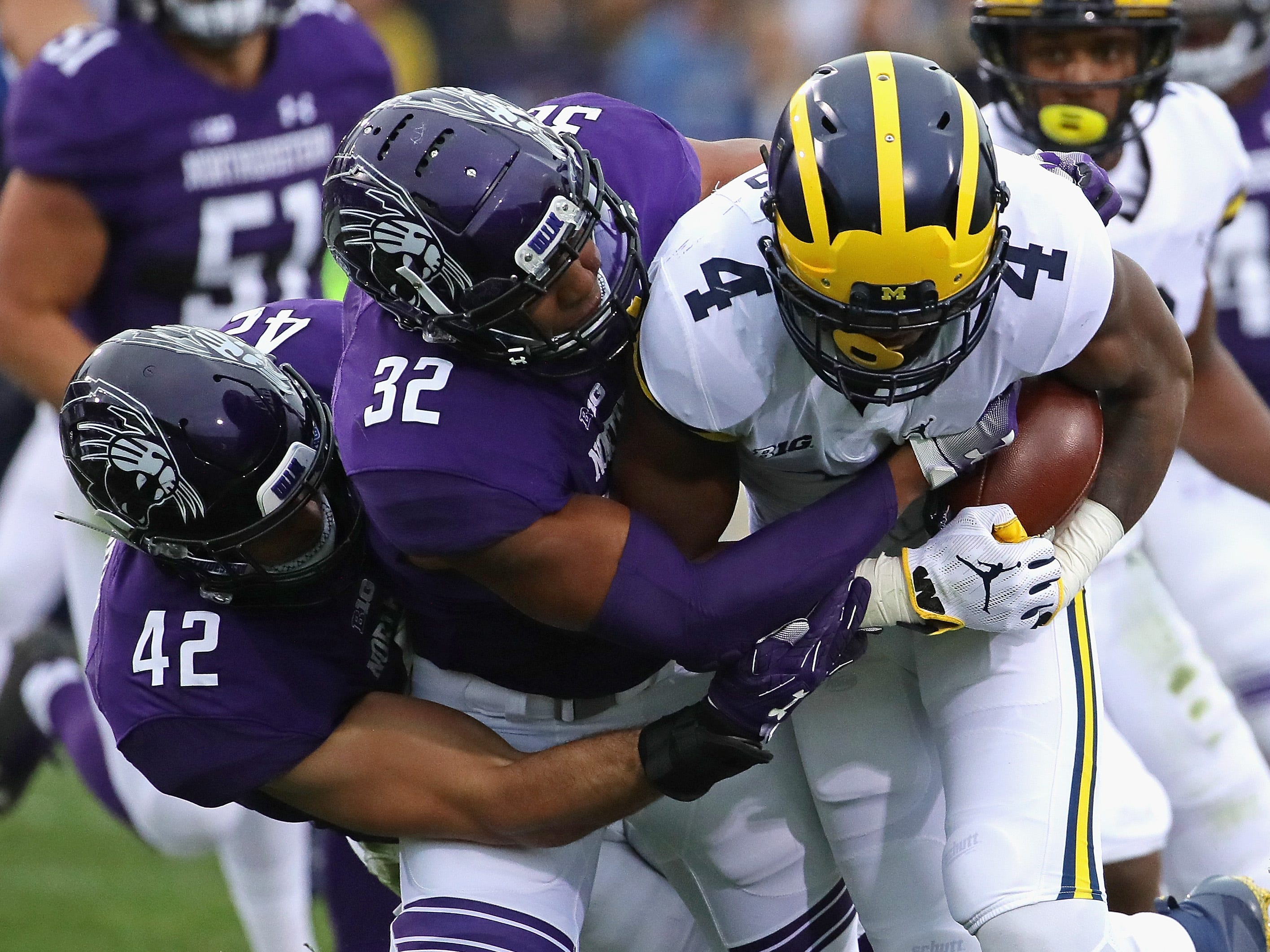 Northwestern's Paddy Fisher (42) and Nate Hall (32) tackle Michigan's Nico Collins at Ryan Field on Sept. 29, 2018 in Evanston, Ill.