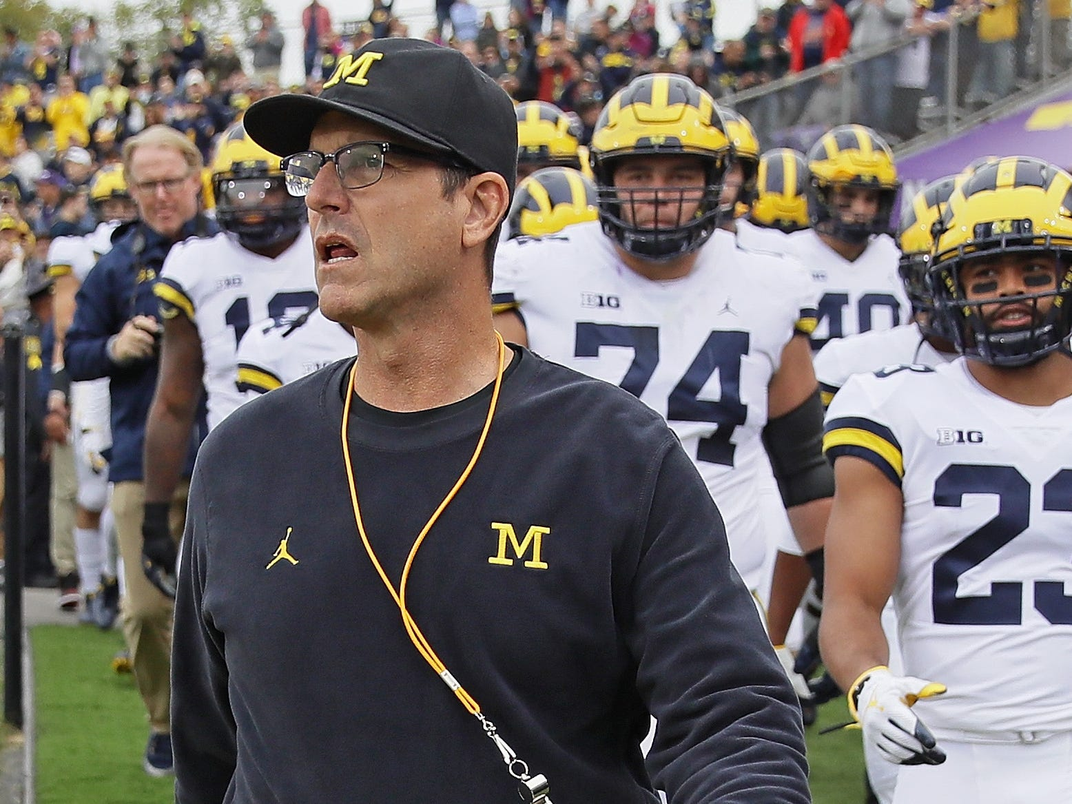 Michigan coach Jim Harbaugh leads his team onto the field before the game against Northwestern on Sept. 29, 2018 in Evanston, Ill.