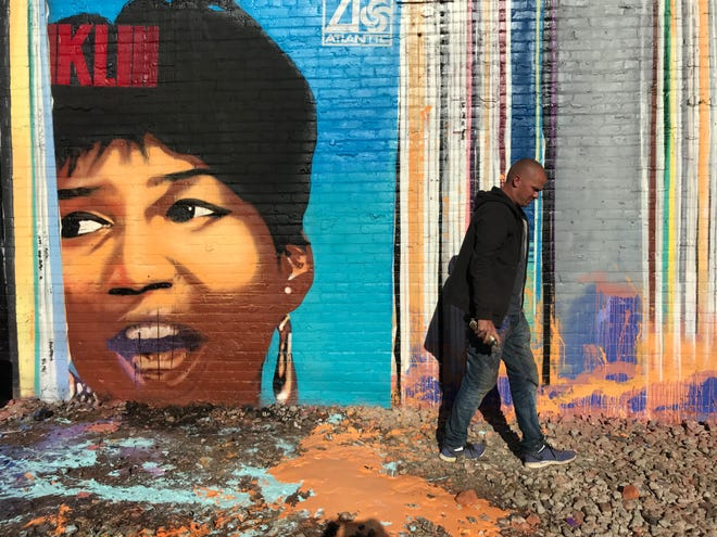 Artist Richard Wilson fixes up his mural featuring Aretha Franklin after he discovered it damaged on Saturday, Sept. 29, 2018, in Detroit's Eastern Market.