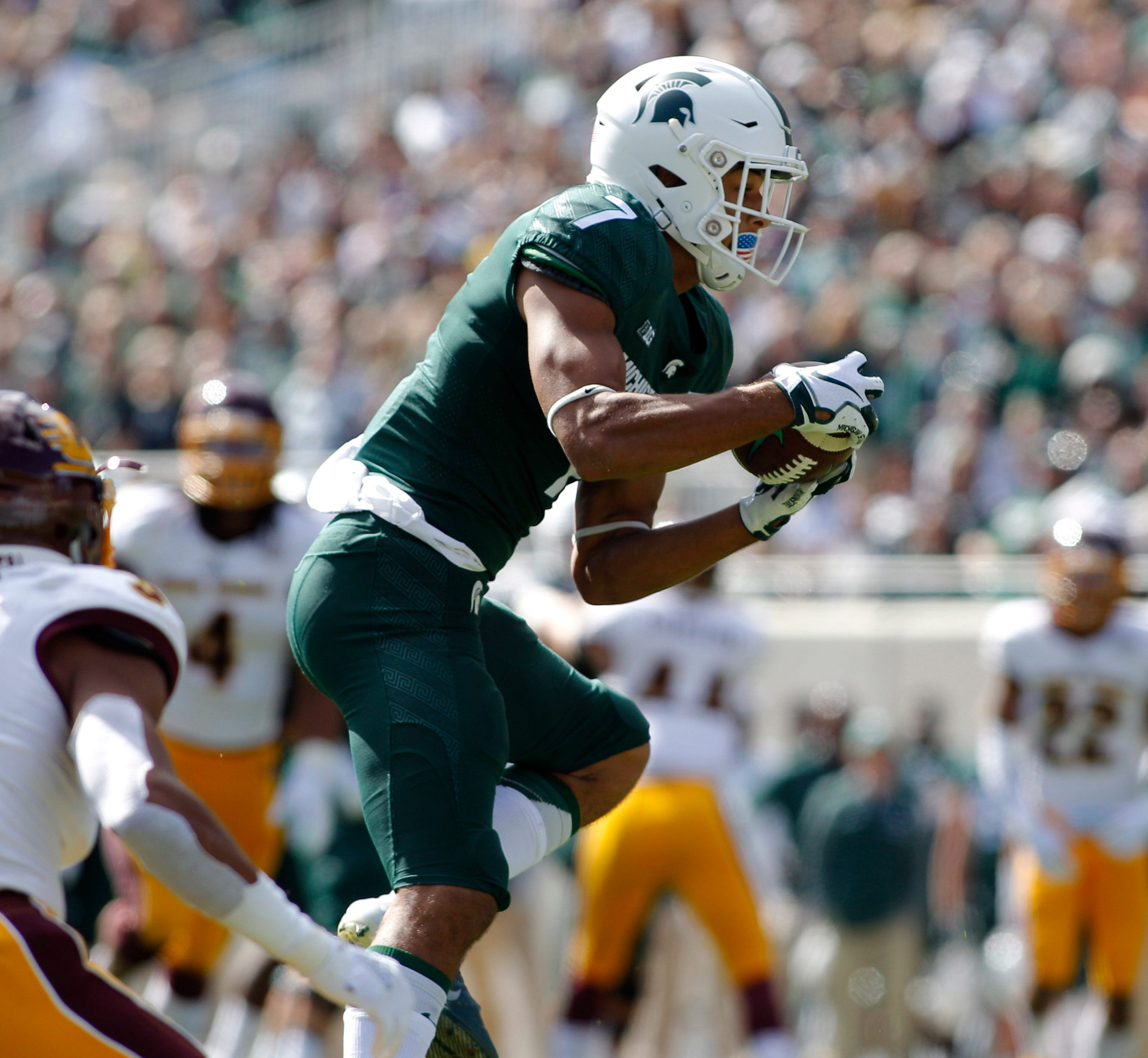 Michigan State's Cody White, right, catches a pass against Central Michigan's Sean Bunting during the second quarter on Saturday, Sept. 29, 2018, at Spartan Stadium.