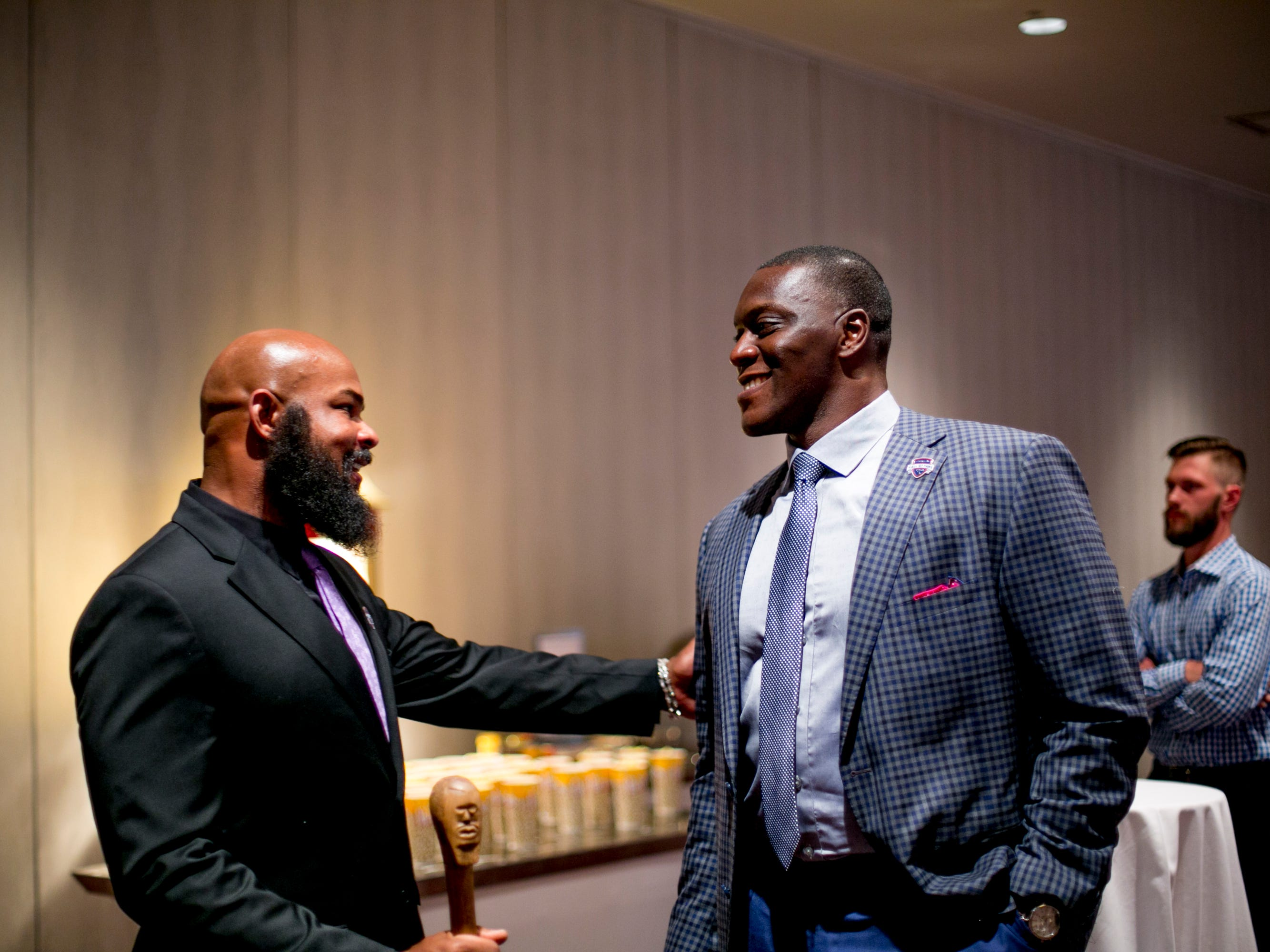 Former MSU running back T.J. Duckett (left) speaks to former Detroit Lions defensive end Robert Porcher before both were inducted into the Michigan Sports Hall of Fame.