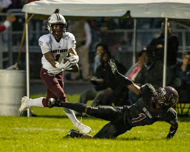 River Rouge's Xavier Smith, left, attempts to catch the ball as Harper Woods' Jordan Anderson defends during a Friday's Week 6 matchup.