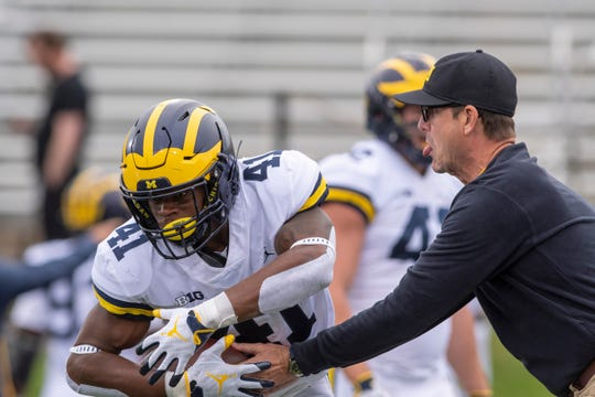 Michigan head coach Jim Harbaugh hands the ball off to running back Christian Turner during pregame warmups last season.