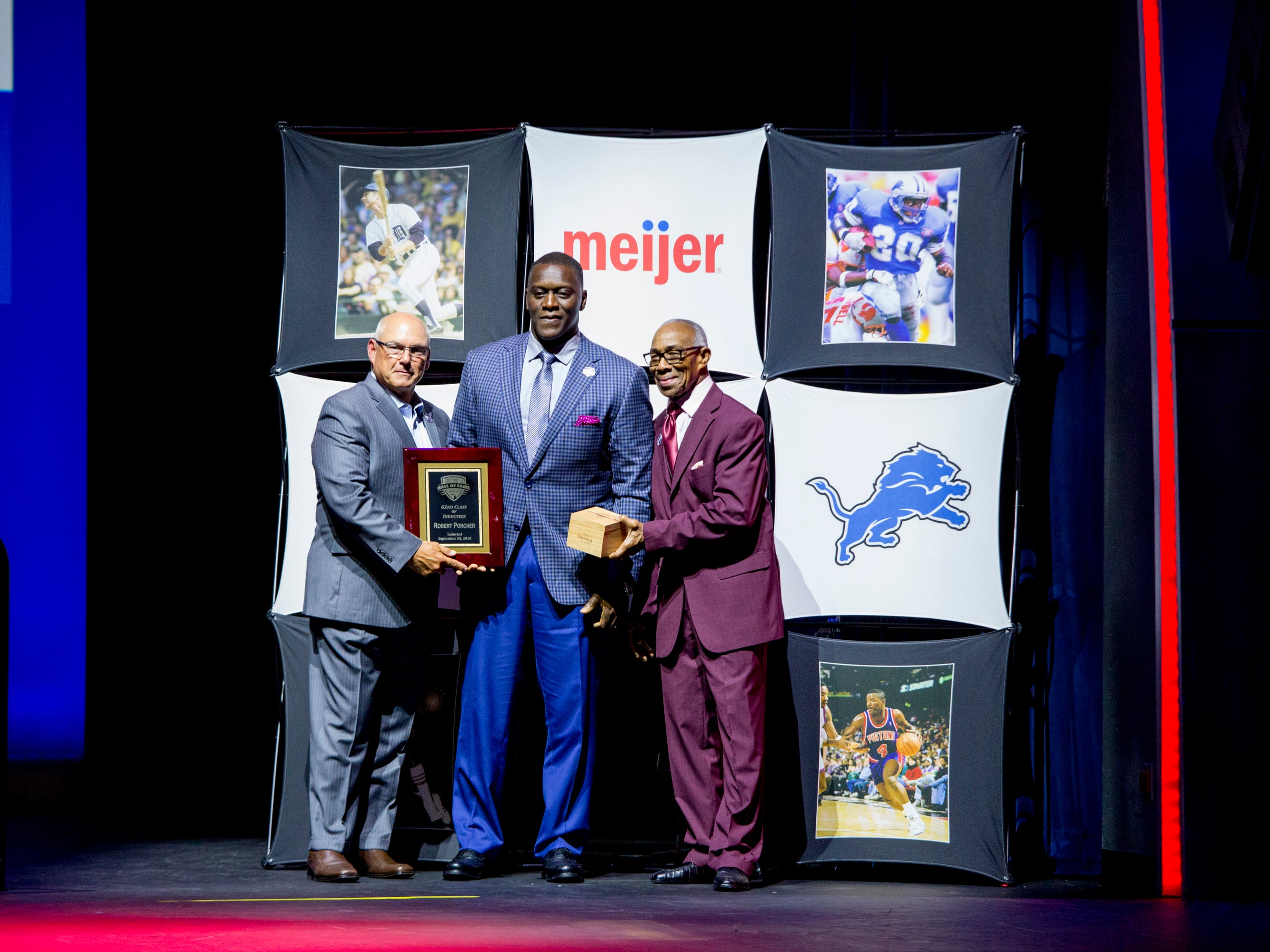 Former Detroit Lions defensive end Robert Porcher receives his award. With him is fellow Lions great Lem Barney (right).