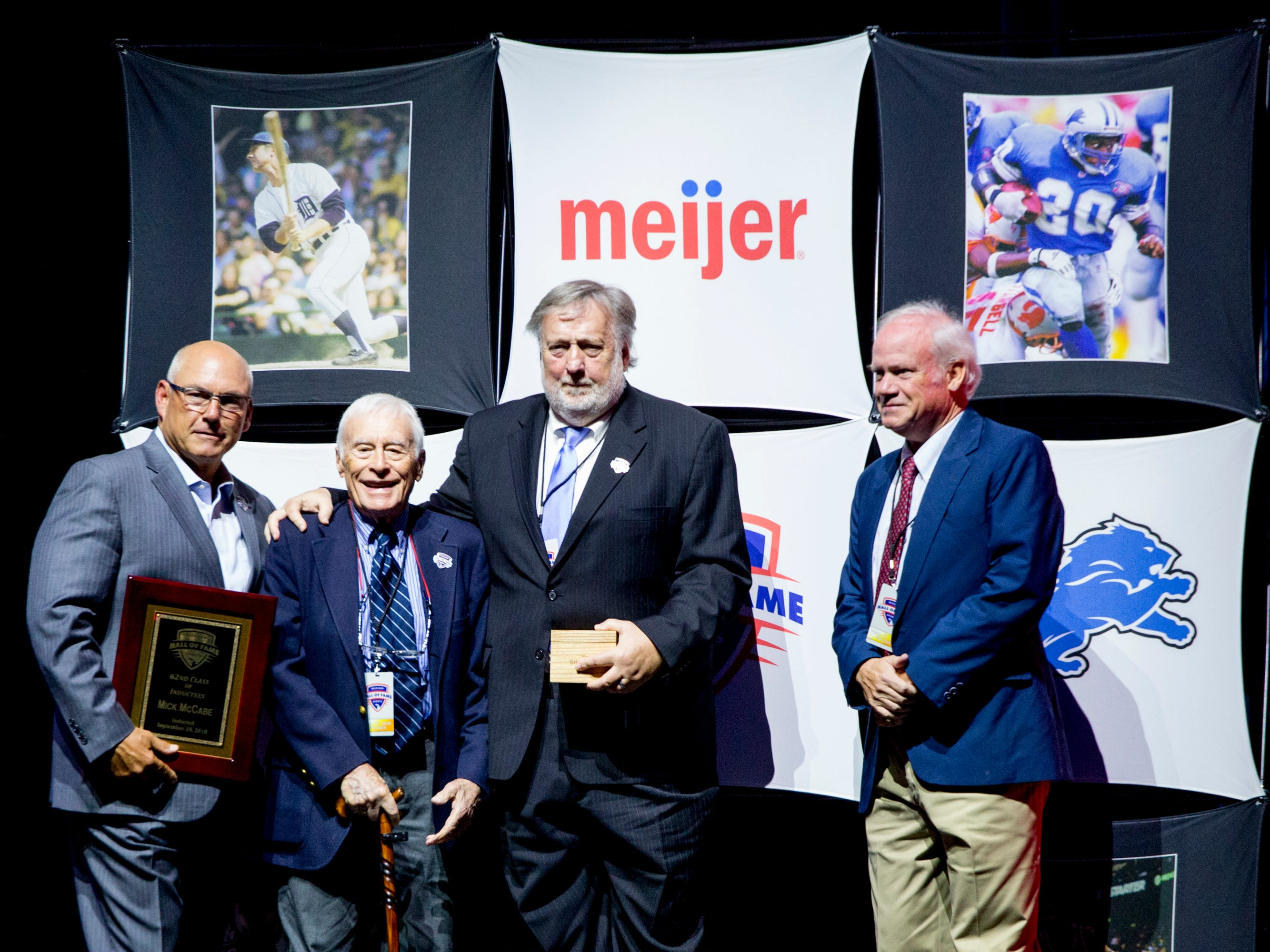 Sports journalist and 2018 Michigan Sports Hall of Fame inductee Mick McCabe receives his award, flanked by fellow veteran sports journalists Mike Green (left) and Tom Gage (right).