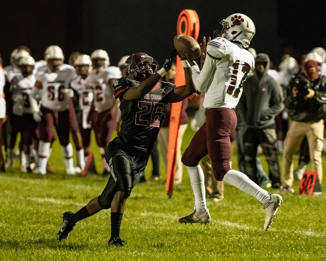 River Rouge receiver R'montaye Caldwell makes an amazing catch as Harper Woods' Da'Veon Turner defends during the first half.
