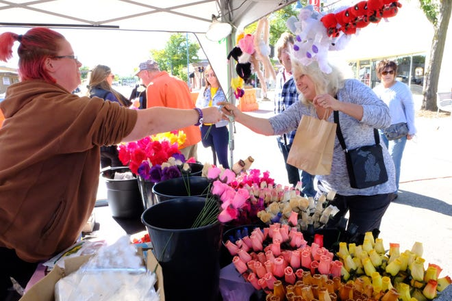 Kim Brinsden, from Dearborn Heights, buys wood-made flowers at the Made in Michigan Festival in Allen Park on Sept. 29, 2018.