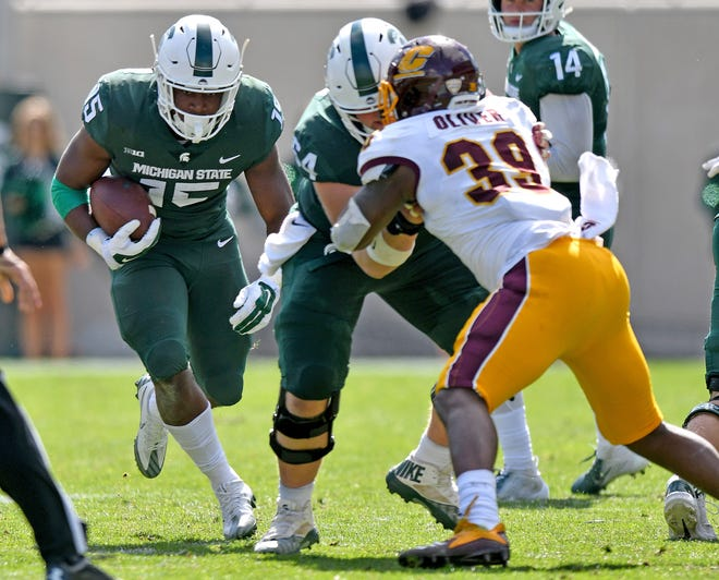 Michigan State running back La'Darius Jefferson, left, sprints through a hole created by offensive lineman Matt Allen in the second quarter on Saturday.