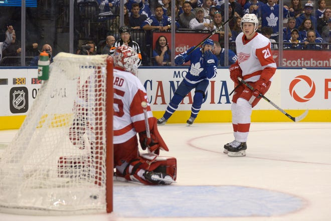 Toronto Maple Leafs' Par Lindholm, rear, scores against the Detroit Red Wings' Jimmy Howard, left, during the second period on Friday.