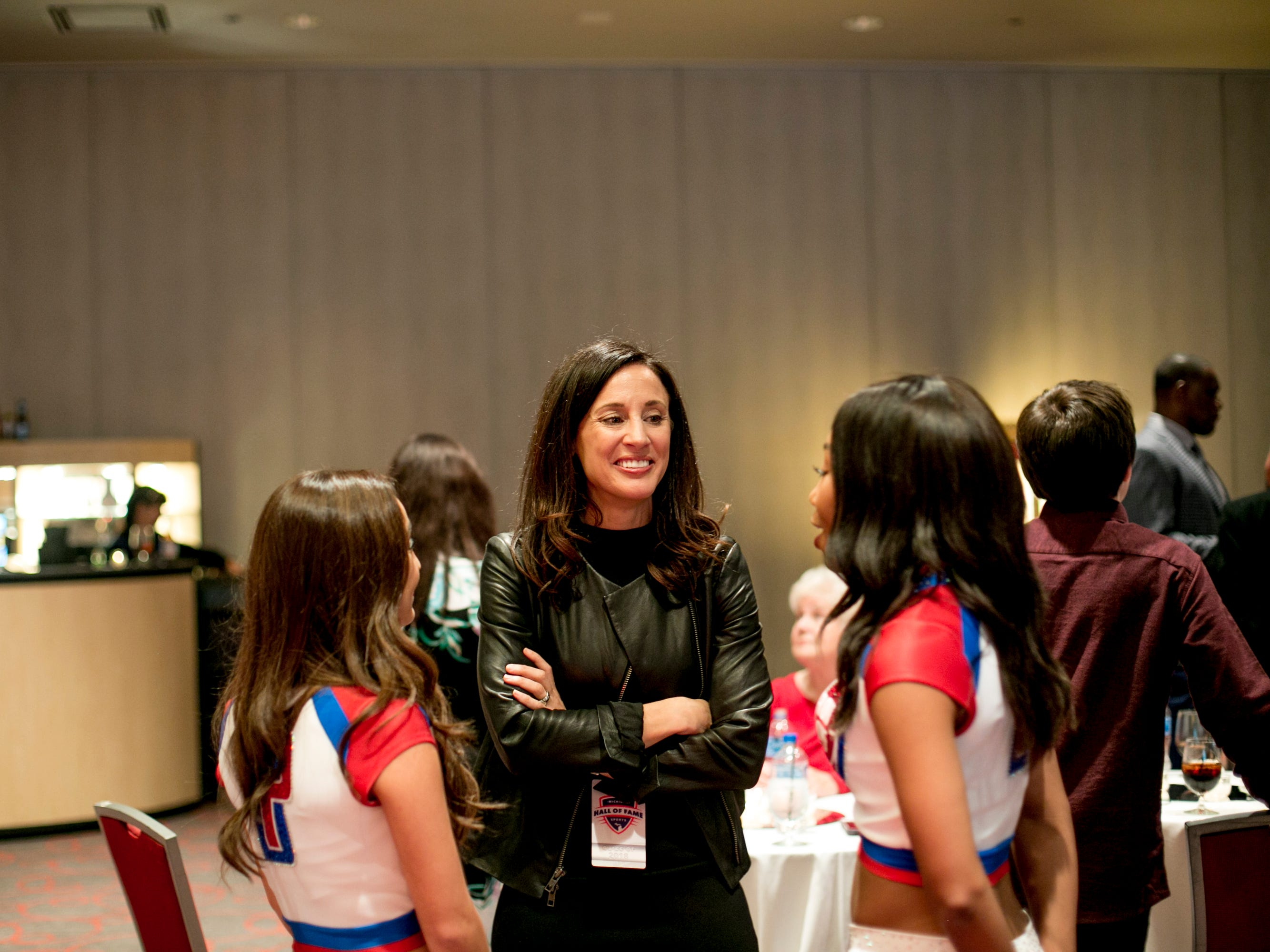 Former Olympic soccer players Kate Sobrero Markgraf speaks to the a pair of Detroit Pistons cheerleaders before the ceremony.