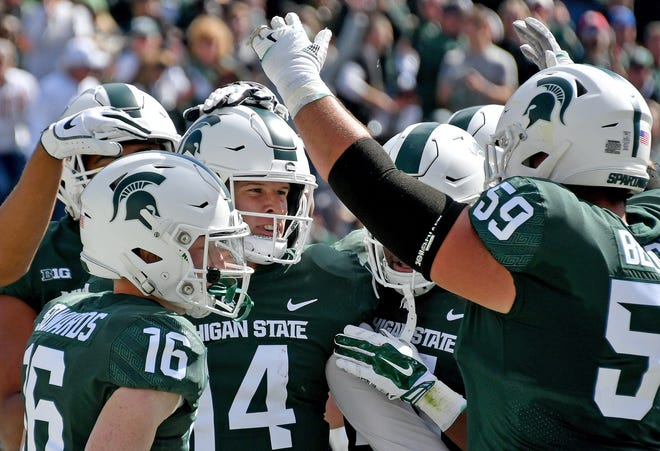 Michigan State quarterback Brian Lewerke and his teammates celebrate a second touchdown during Saturday's game against Central Michigan.
