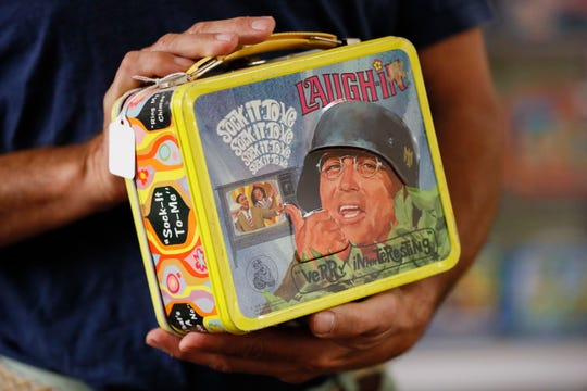 A vintage lunch box is handled at Main Auction Galleries Inc.