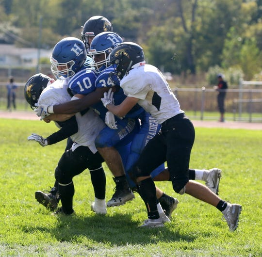 Matthew Robert (10) and Maurice Rankins Jr. (34) of Horseheads combine to tackle Ja'Ovian Fisher of Corning on Sept. 29, 2018 at Horseheads High School.