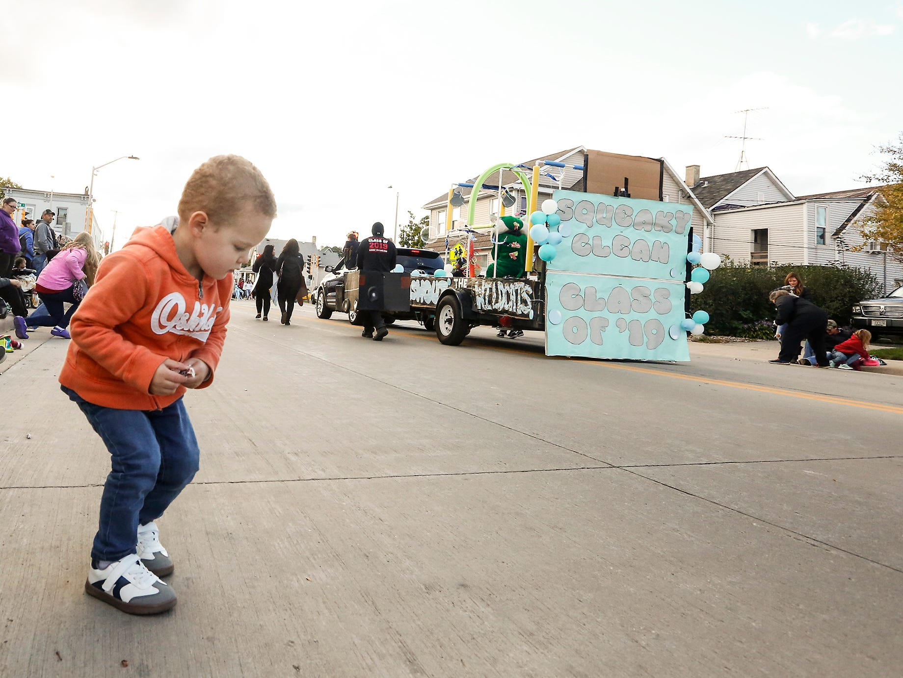 Cole Adams of Fond du Lac gathers candy thrown during the Fond du Lac High School football homecoming parade Friday, Sept. 28, 2018, which went down portions of Martin Avenue and Ninth Street in Fond du Lac, Wisconsin.
