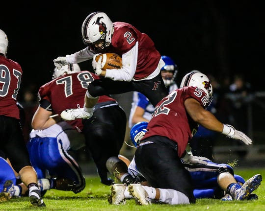 Fond du Lac's Eben Sauer leaps over an Oshkosh West defender Friday night in Fond du Lac.