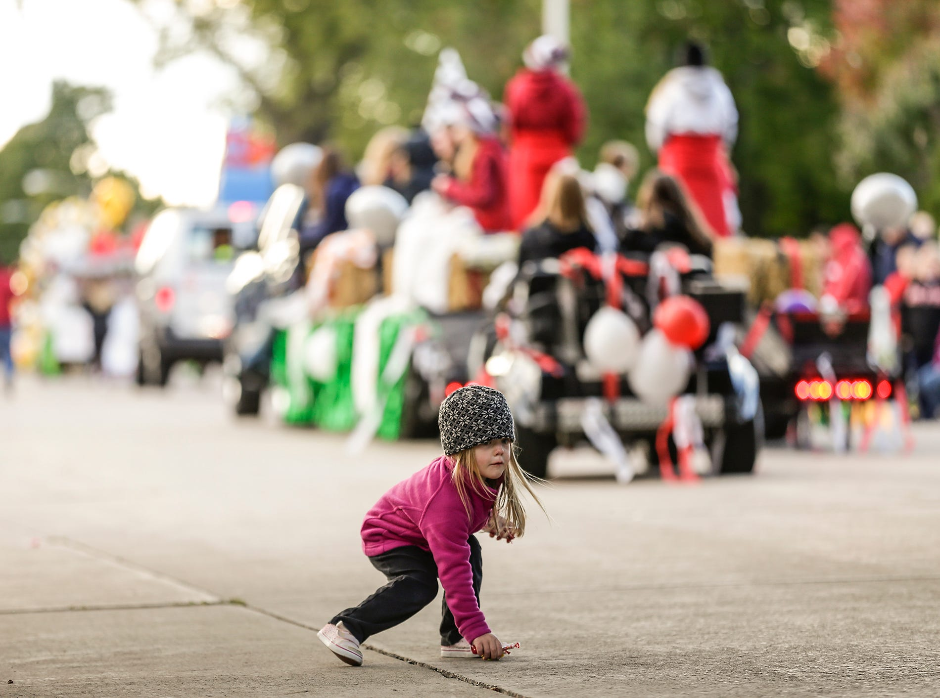 Kinsley Mischo, 3, of Fond du Lac picks up candy during the Fond du Lac High School football homecoming parade Friday, Sept. 28, 2018, which went down portions of Martin Avenue and Ninth Street in Fond du Lac, Wisconsin.
