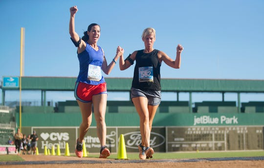 Jen Brooks, left, and Amber Donahue finish the Fort Myers Walk Like MADD and 5K Dash on Saturday at JetBlue Park in south Fort Myers. The friends ran to honor Donahue's father-in-law, Billy Donahue Jr., who was killed by a drunken driver. More than 500 people took part in the annual event hosted by MADD Southwest Florida. MADD stands for Mothers Against Drunk Driving.