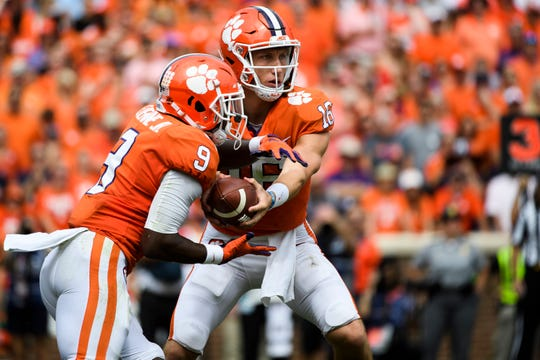 Clemson quarterback Trevor Lawrence (16) hands the ball to running back Travis Etienne (9) at Clemson's Memorial Stadium on Saturday, Sept. 29, 2018