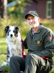 In this Monday, Sept. 17, 2018 photo, Mark Biel, a ranger with Glacier National Park, and Gracie, the 4-year-old service dog who helps keep bighorn sheep and goats a safe distance from visitors to Logan Pass, pose outside their office near Park Headquarters in Glacier National Park, Mont. Gracie launched her Wildlife Working Dog career at the national ;ark in 2016.  Today, the border collie counts about 17,000 followers on Instagram. (Brenda Ahearn/The Daily Inter Lake via AP)