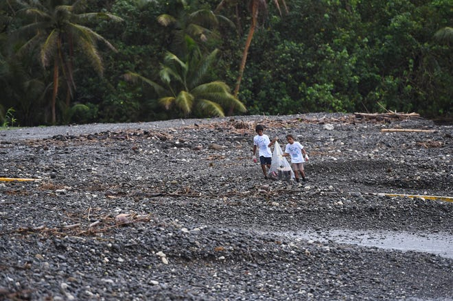 Jayden Cruz, 10, right, and Jaythan Quidachay, 11, hold their garbage bag from blowing away while volunteering in the 24th Guam International Coastal Cleanup at Umatac Bay on Sept. 29, 2018.